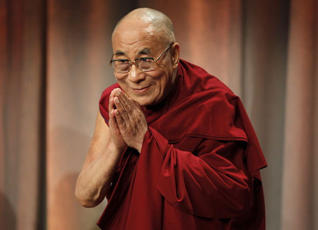 """Tibet's exiled spiritual leader the Dalai Lama greets the audience as he arrives at a talk titled """"Beyond Religion: Ethics, Values and Wellbeing"""" in Boston"""